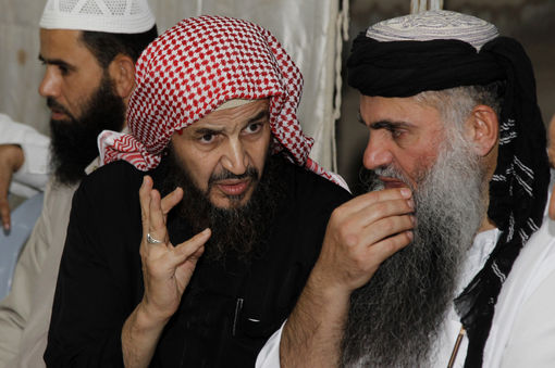 Radical Muslim cleric Abu Qatada listens to Islamist scholar Sheik Abu Mohammad al Maqdisi during a celebration after his release from a prison near Amman